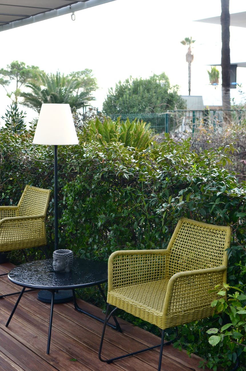 terrace with stylish wicker furniture in tropical resort on rainy day